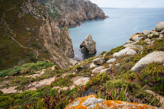 Cabo da Roca travel destination located in Sintra, Portugal. Hidden rocky rough beach surrounded by