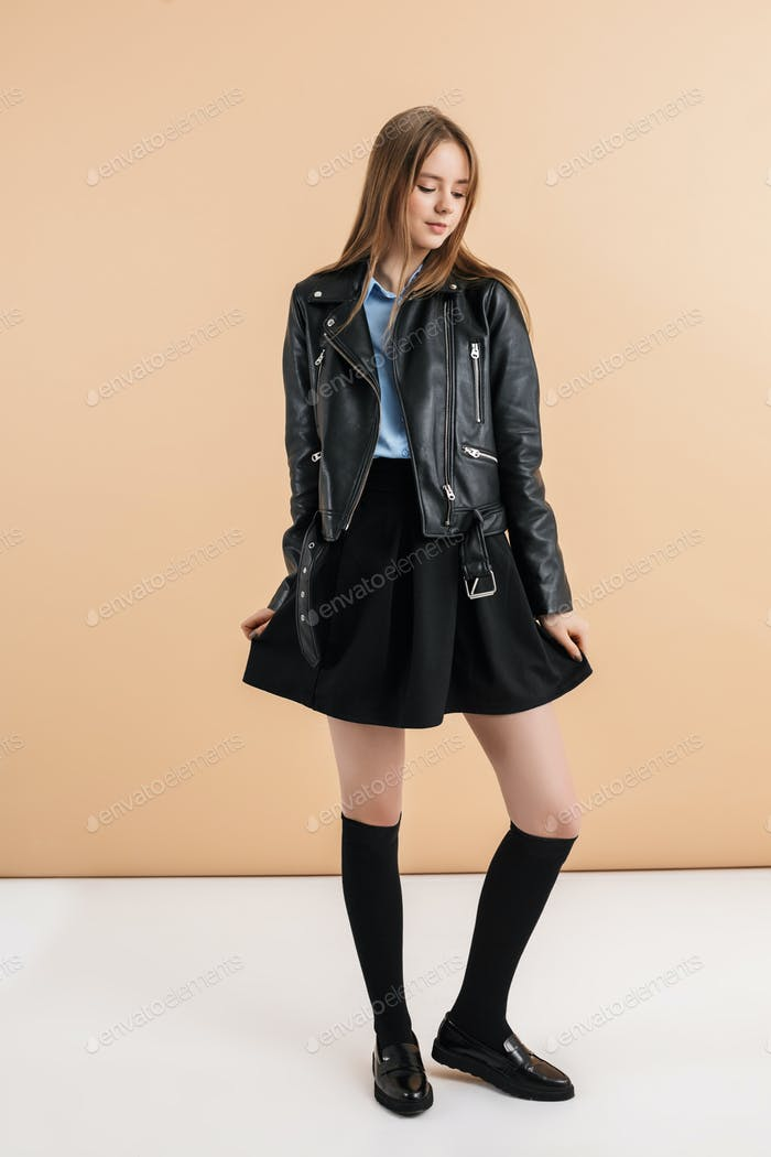 Young beautiful smiling girl with two braids in leather jacket and skirt dreamily looking aside