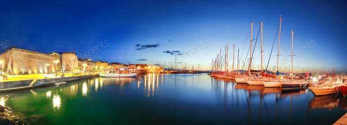 Night view of the Alghero Marina yacht port at the Gulf of Alghero with anchored sailboats