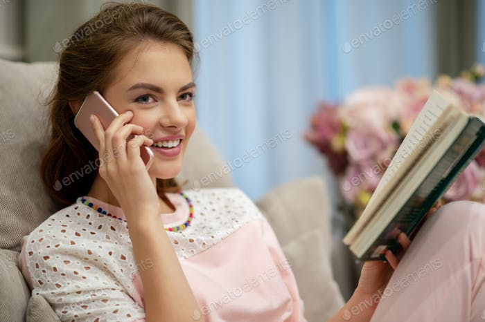 Happy young woman talking by smart phone at home.
