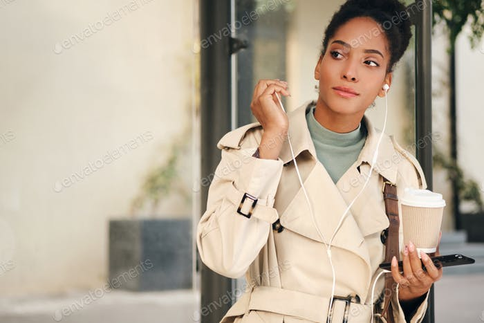 African American girl in stylish trench coat with coffee and cellphone waiting bus at bus stop