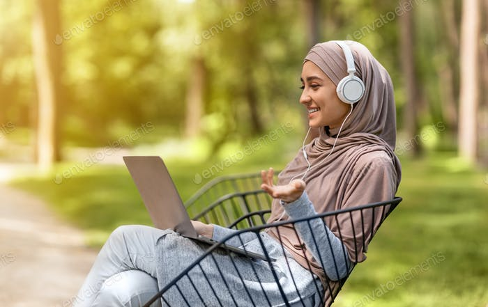 Happy muslim girl having videocall while resting at park