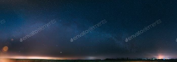 Night Starry Sky With Glowing Stars Above Countryside Landscape. Milky Way Galaxy And Rural Field