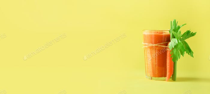 Fresh organic carrot juice with carrots, celery on yellow background. Vegetable smothie in glass