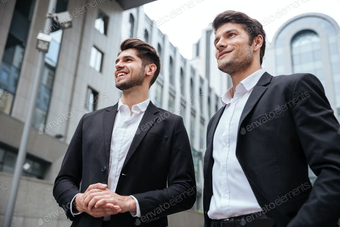 Two businessmen standing near business center