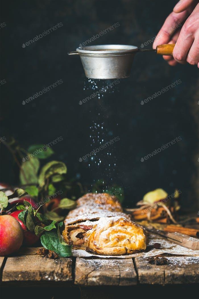 Mannes Hände bestreuen Zuckerpulver auf Apfelstrudel Kuchen