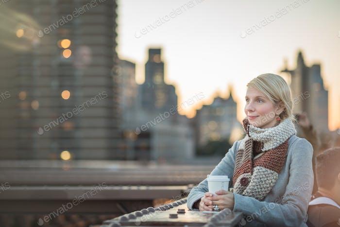Mujer en el Puente de Brooklyn mirando a Manhattan con un café