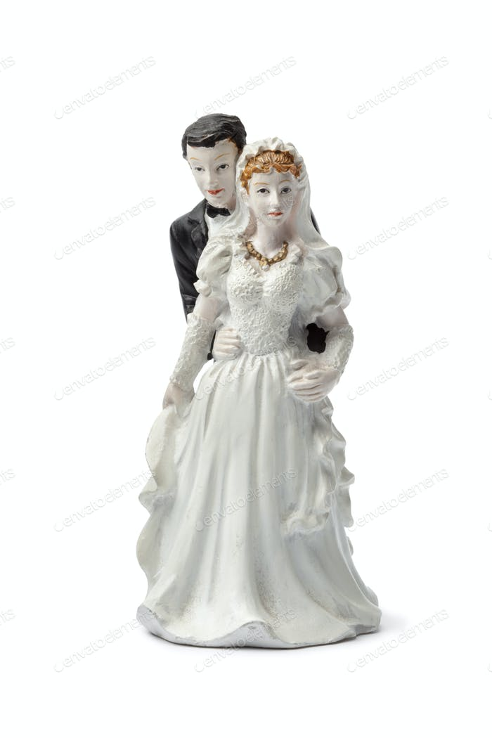 Old plaster bride and groom cake topper isolated on white back