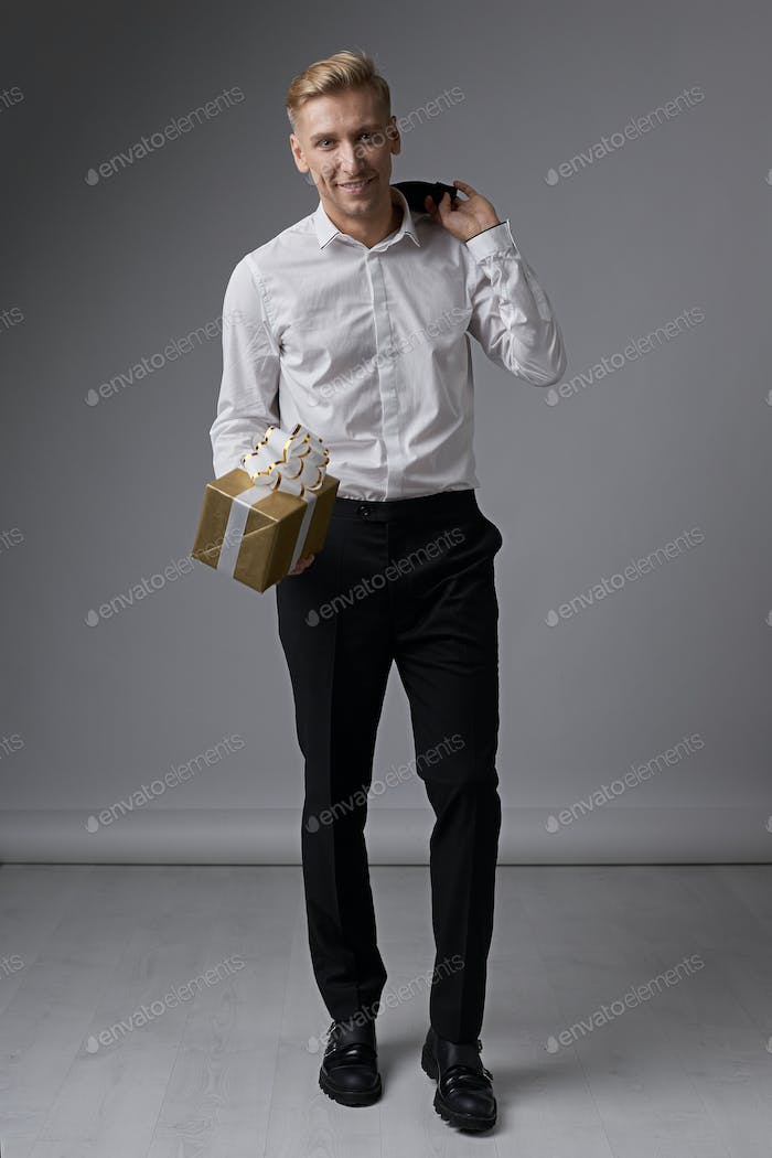 Stylish businessman holding gift box
