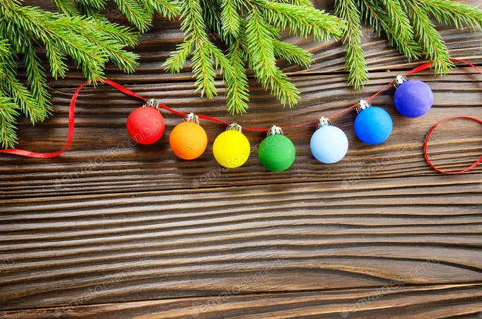 Christmas background of spruce branches and colorful balls on wo