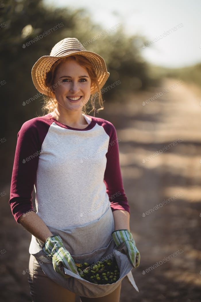 Portrait of smiling young woman collecting olives at farm