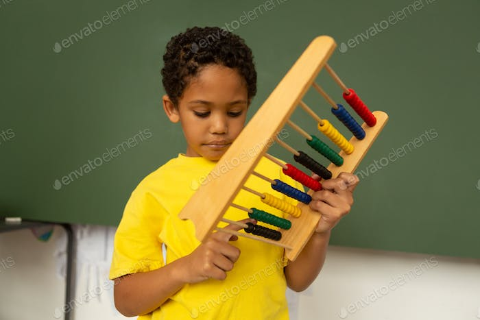 Thoughtful mixed-race schoolboy learning mathematics with abacus in a classroom at elementary school