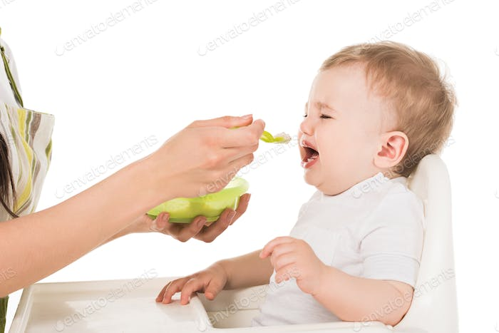 cropped image of mother in apron feeding crying baby boy in highchair isolated on white background