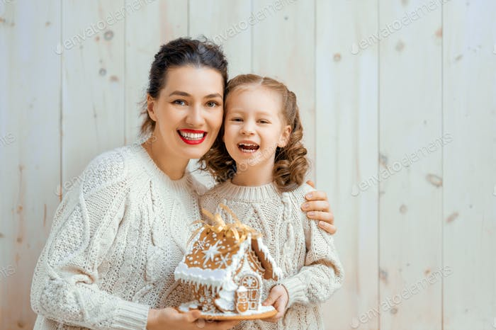 girl and mother with Christmas gingerbread house