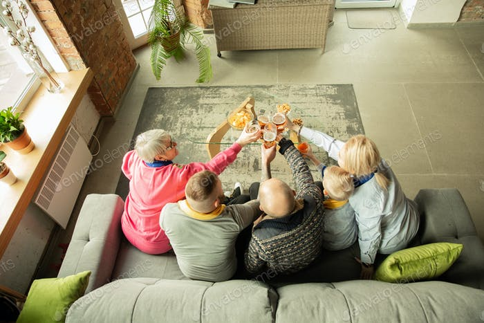 Excited family watching football, sport match at home, top view