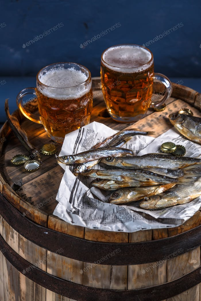 Beer mugs with dried fishes on a wooden barrel