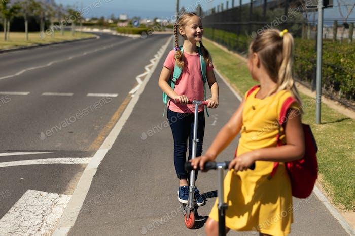 Caucasian schoolgirls riding push scooters