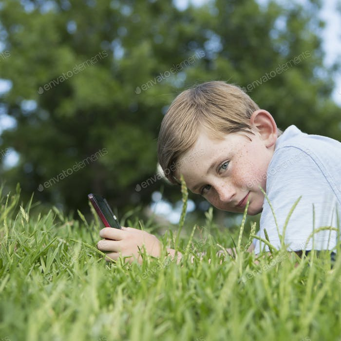A young boy sitting on the grass using a hand held electronic games device.
