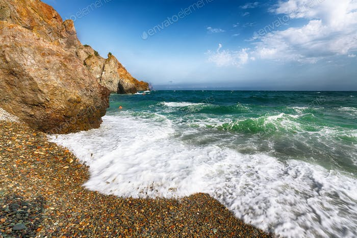 Sea waves crashing on the shore and flowing above seashore pebbl
