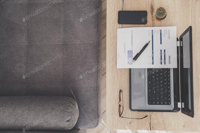 Draufsicht des Home-Office-Arbeitsplatzes. Laptop, Rechnung und Brille auf Holztisch, Sofa