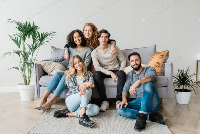 Happy young casual couple and their friends sitting in front of camera