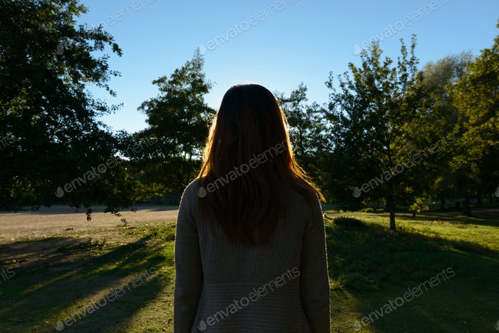 Rear view of young Asian woman looking towards grassy plain with nature