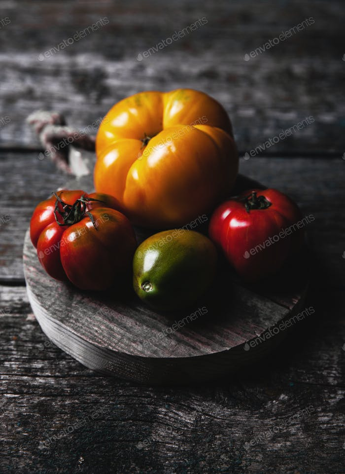 Composition with delicious tomatoes, wooden board and products on grey background, healthy food