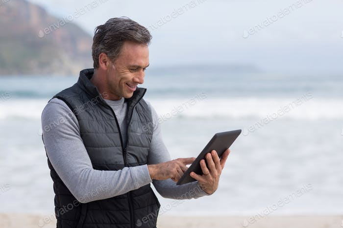 Mature man using digital table on the beach