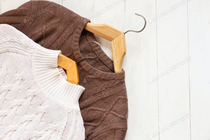 Zwei gestrickte Pullover auf Kleiderbügeln auf weißem Holzhintergrund von oben flach liegen.