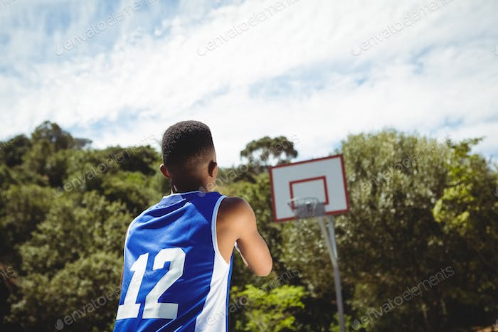 Rear view of teenage boy practicing basketball