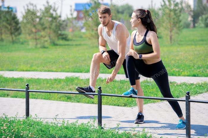 Young Couple Stretching Legs Outdoors