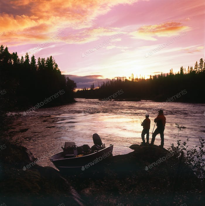 Two people standing on the shore fishing at dusk.