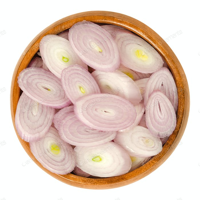 Sliced shallots in wooden bowl over white