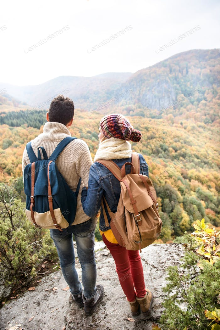 Beautiful couple with backpacks against colorful autumn forest