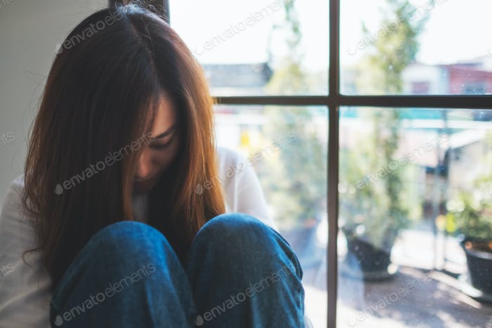 A sad young woman sitting alone in the room