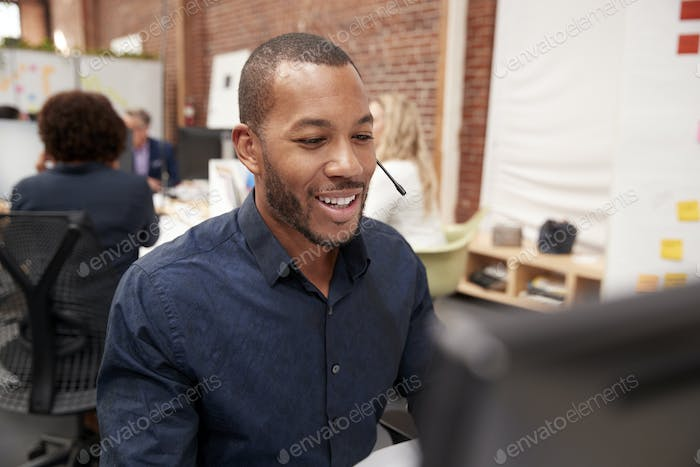 Male Customer Services Agent Working At Desk In Call Center