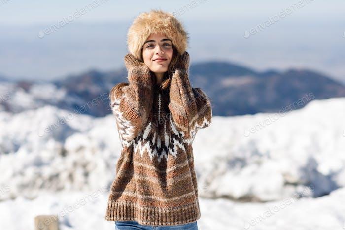 Mujer joven disfrutando de las montañas nevadas en invierno