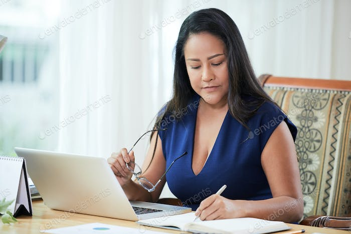 Confident adult businesswoman working at desk