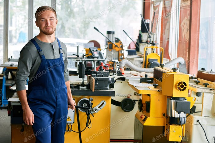 Young Workman Smiling at Camera in Shop