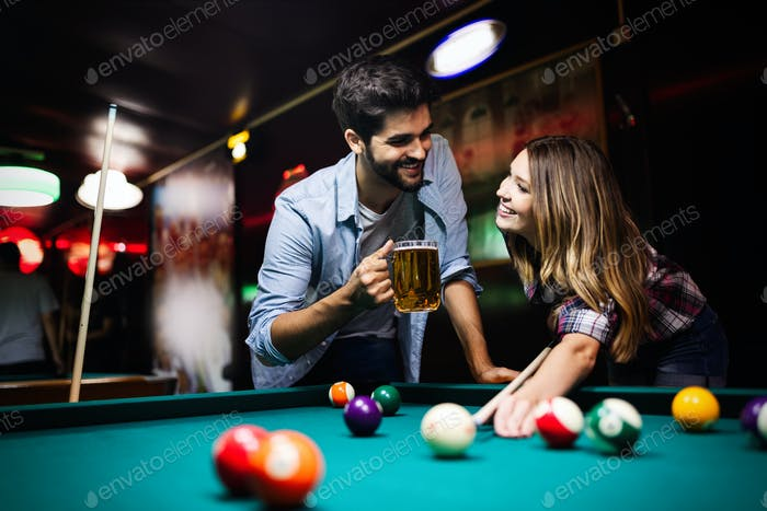 Happy young man playing snooker with his girlfriend. Happy loving couple