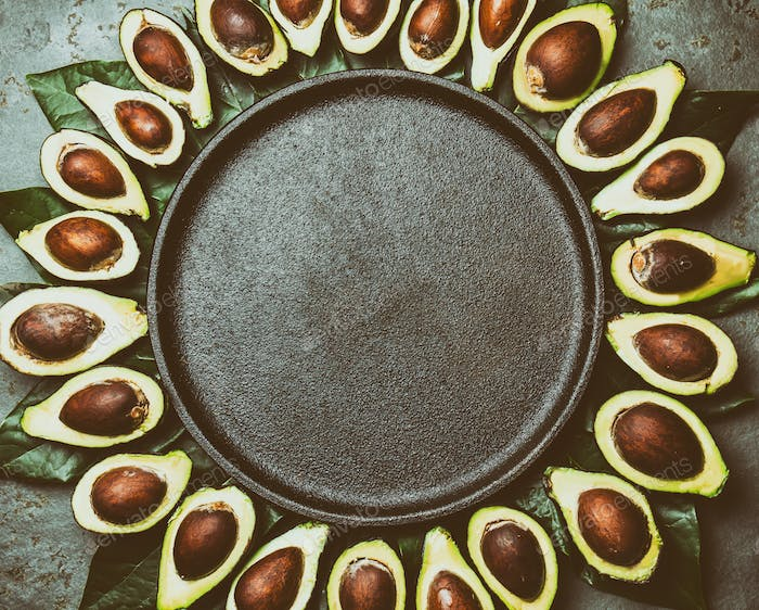 Food Background with Avocado and Avocado Tree Leaves. Copy Space
