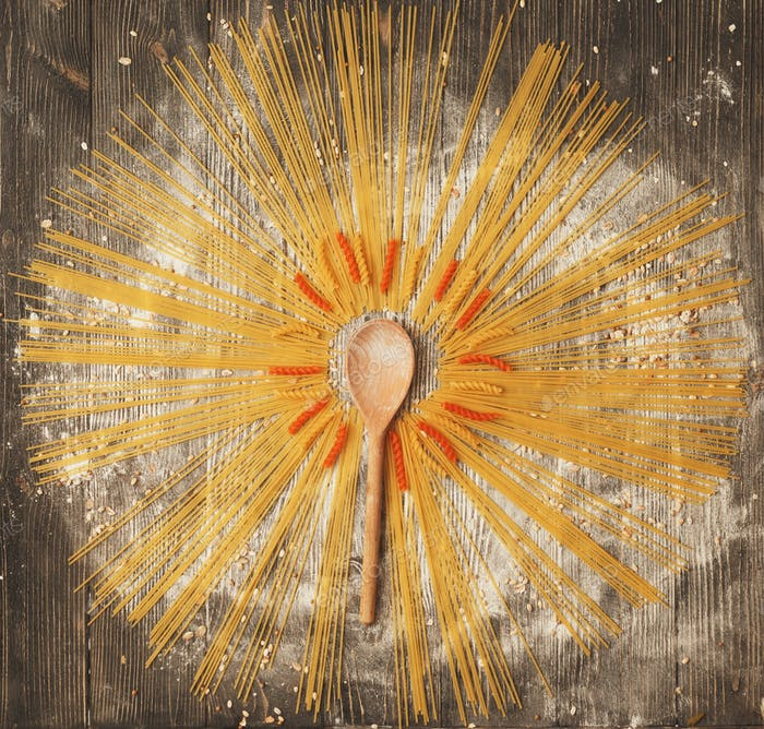 Spaghetti laid creative housewife in the form of the sun on a dark wooden background