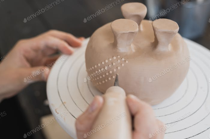 Young woman attaching clay product part to future ceramic product. Pottery workshop