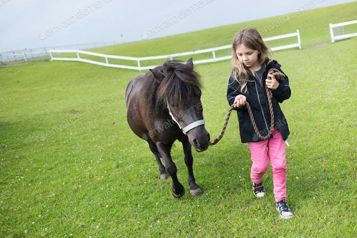 Girl (4-5) walking with pony