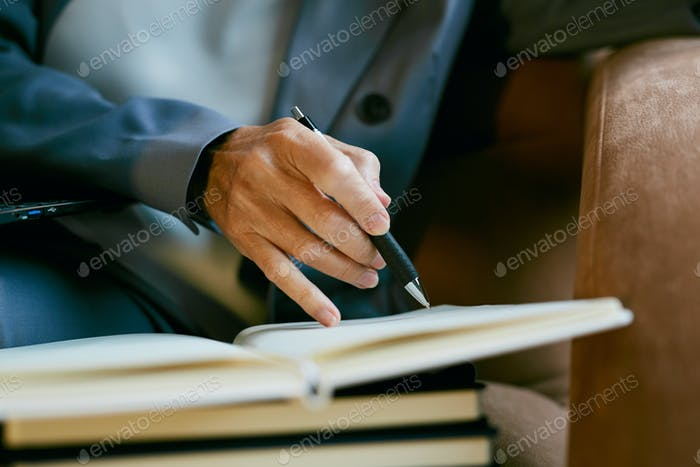 Businesswoman Writing in Planner Close up