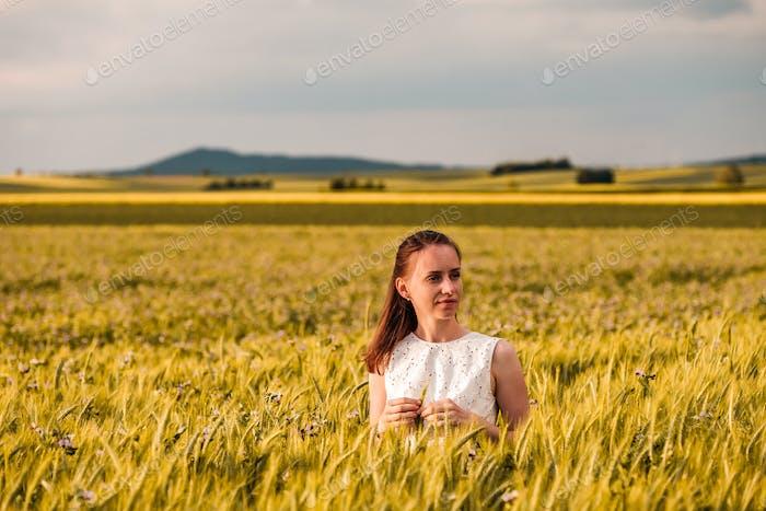 Beautiful woman in white dress on golden yellow wheat field