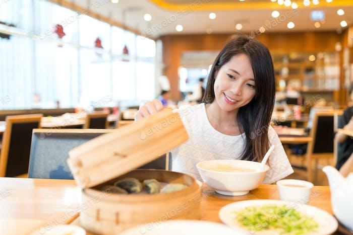 Frau öffnen Sie den Bambus Dampfer im chinesischen Restaurant