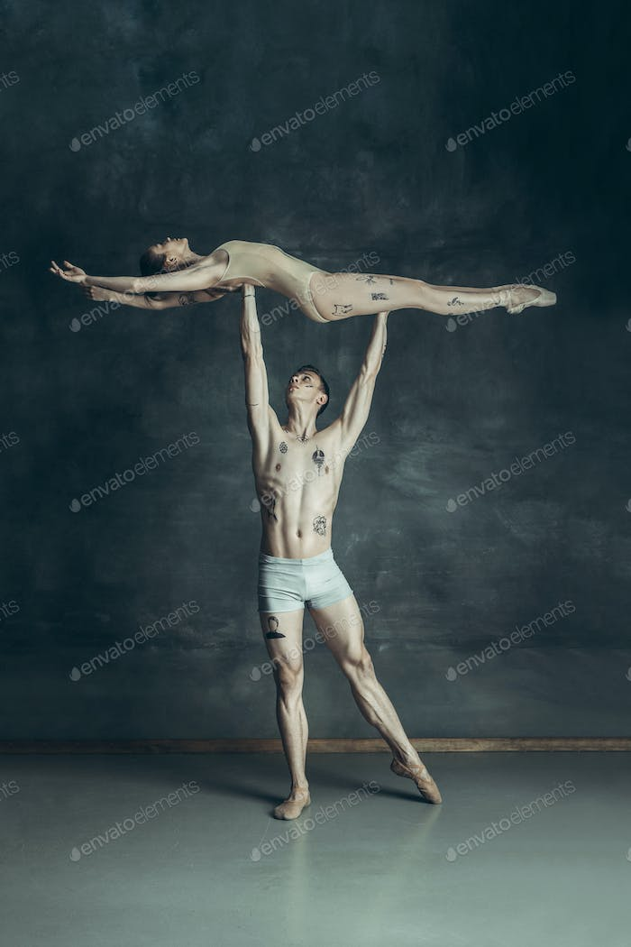 The young modern ballet dancers posing on gray studio background