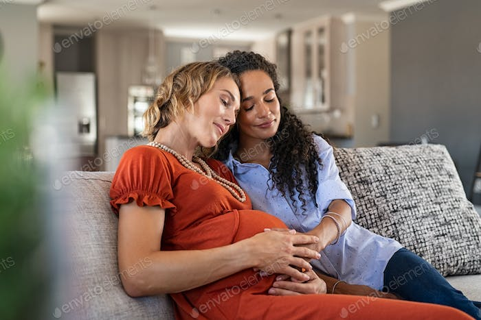 Lovely pregnant lesbian couple at home