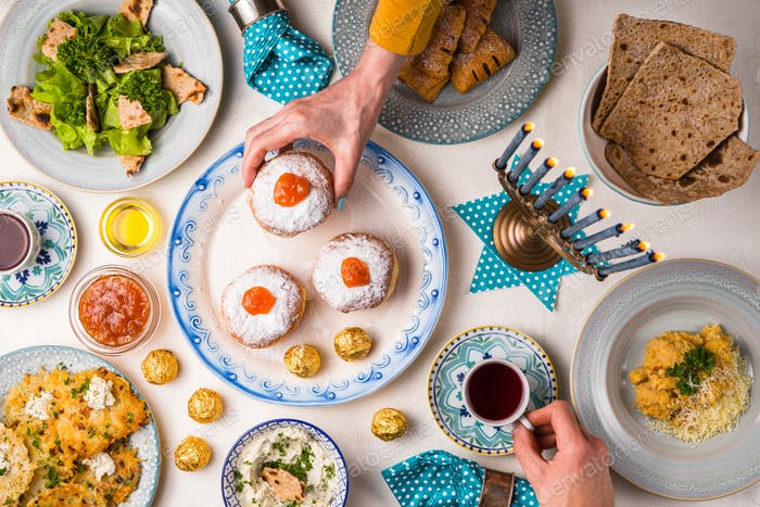 Jewish holiday Hanukkah, traditional feast, hands above table top view